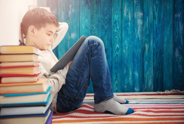 Child Reading Books as Part of a Summer Reading Program
